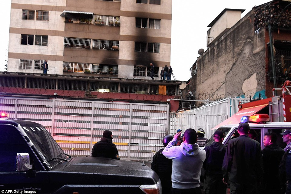 Security forces and members of the Bolivarian National Intelligence Service check the Residencias Don Eduardo apartment building. This could have been damaged by one of the drones or by a gas tank explosion