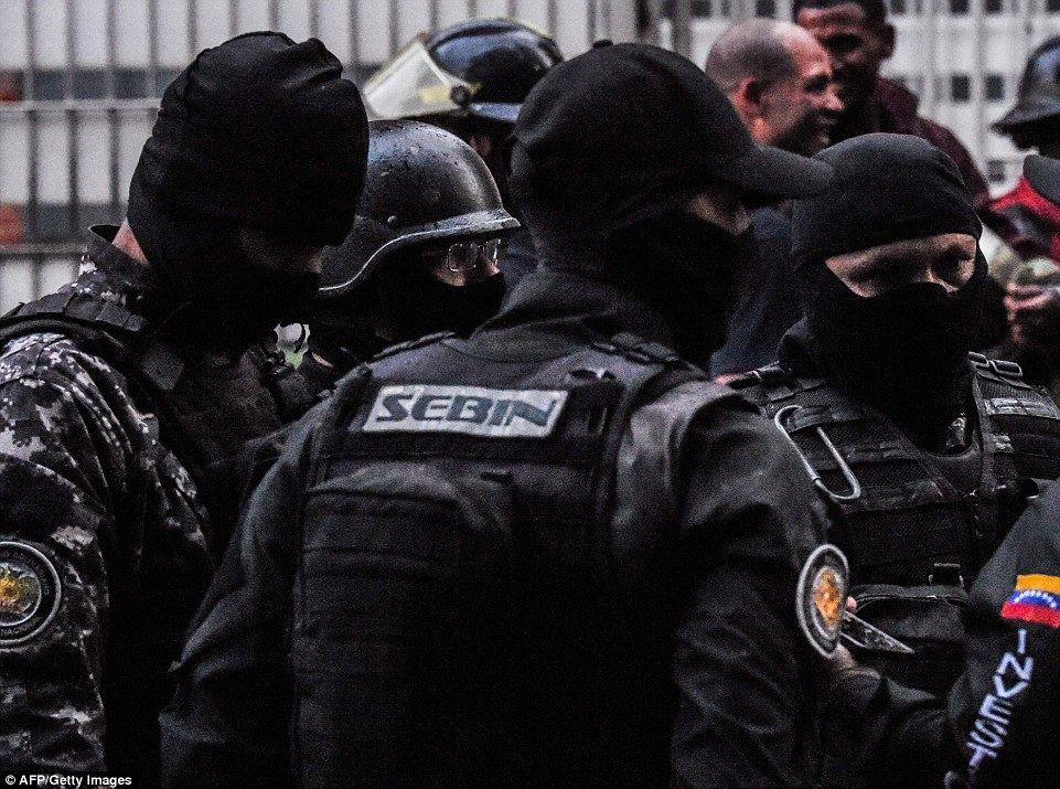 Heavily armed security forces check a building after the explosions were heard on Saturday, in an incident Maduro
