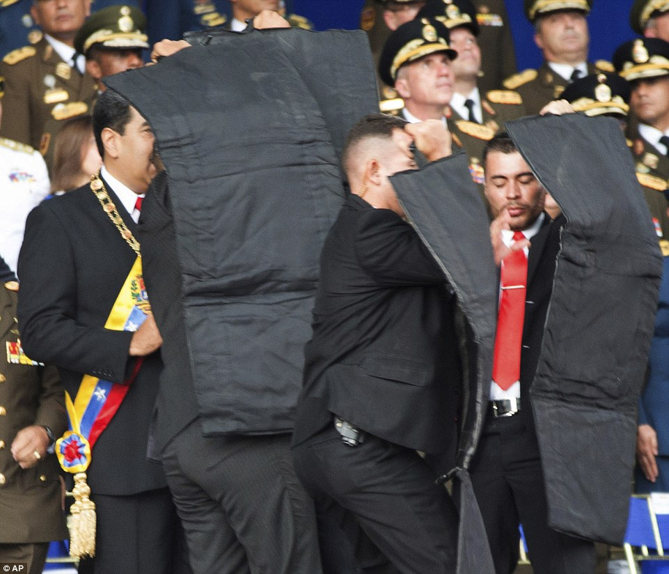 Security personnel shield Maduro after the explosions, which came when he was addressing a celebration to mark the National Guard