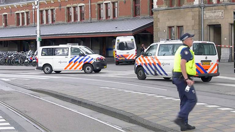 In this image made from video, Dutch police officers stand near the scene of a stabbing attack near the central daily station in Amsterdam, the Netherlands, Friday Aug. 31, 2018. Police the Dutch capital shot and wounded a suspect Friday following a stabbing at the central railway station. Amsterdam police said in a series of tweets that two people were injured in the stabbing and the suspect was then shot by officers.