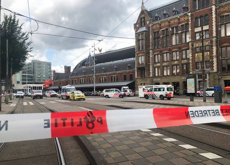 Dutch police officers near the scene of a stabbing attack near the central daily station in Amsterdam, the Netherlands, Friday Aug. 31, 2018. Police the Dutch capital shot and wounded a suspect Friday following a stabbing at the central railway station. Amsterdam police said in a series of tweets that two people were injured in the stabbing and the suspect was then shot by officers.