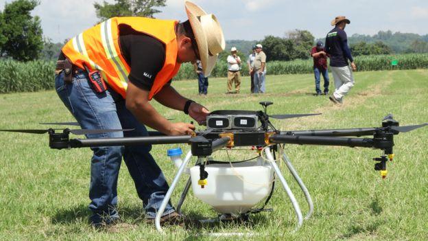 Man assessing crop-spraying drone