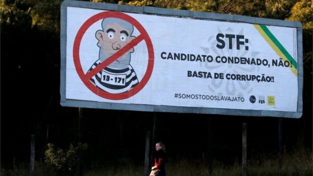 "A woman walks past a billboard which reads: ""No to convicted candidates! Stop corruption!""."