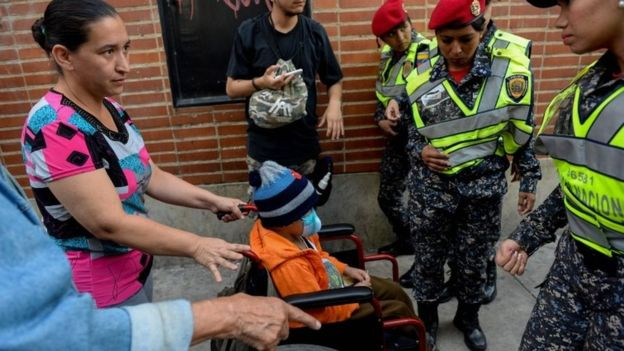 "A woman pushing a wheelchair with a child at a health workers protest outside the ""Dr J M de los Rios"" Children"